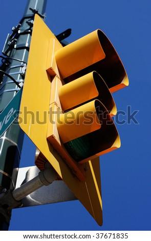 yellow street light against blue sky - stock photo