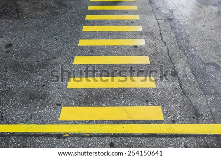 Yellow stripes crosswalk on the old concrete surface