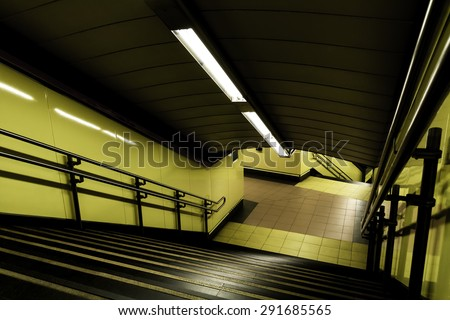 Yellow subway tunnel with a stair set in Madrid - stock photo