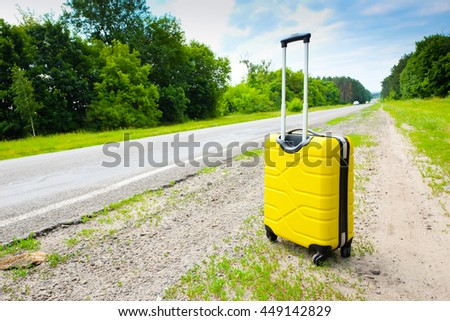 Yellow suitcase on the road. Travel concert