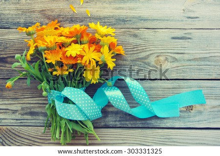 Yellow summer flowers on a wooden surface. Bouquet from a marigold with a blue tape. Calendula flowers. Holidays bouquet - stock photo
