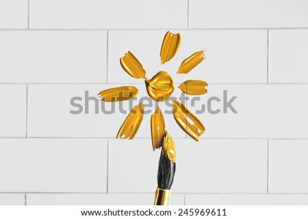 Yellow sun painted on white brick wall as a background - stock photo