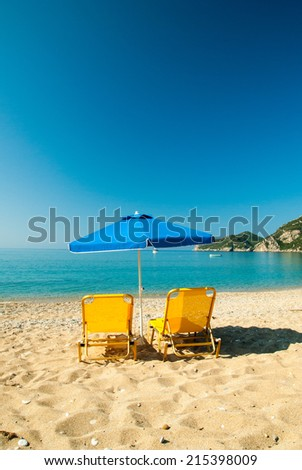 Yellow sunbeds and blue umbrella on a beautiful beach in Corfu Island, Greece Parasols and sunbeds into the sun on a tropical beach.