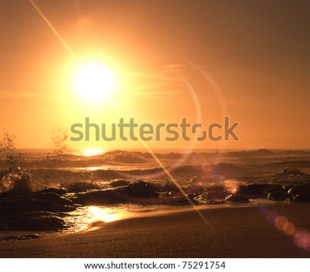 yellow sunrise over sandy beach and ocean waves - stock photo