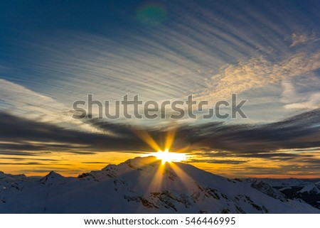 yellow sunset over the peak of a french alpine mountain