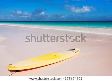 Yellow surfboard at tropical beach on Bahamas - stock photo