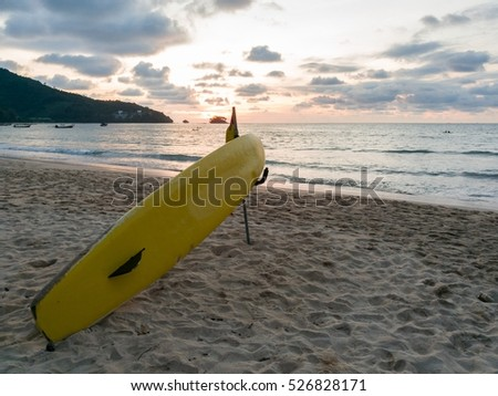 yellow surfboard on the beach with sunset background at Nai Yang beach in phuket, Thailand