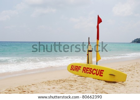 yellow surfborad for rescue and red flag on beach