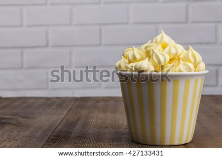 Yellow Sweets on wood table and white brick background - stock photo