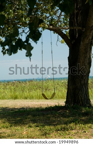 Yellow swing by the see, no one around - stock photo