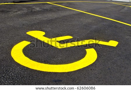 Yellow symbol for designated parking for handicapped driver - stock photo