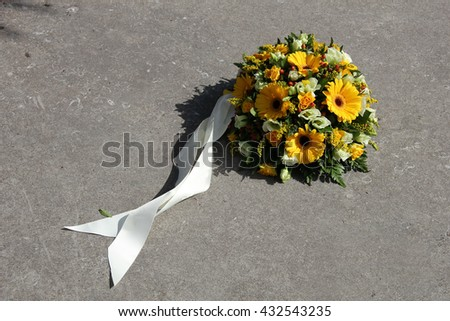yellow sympathy flowers on a tombstone - stock photo