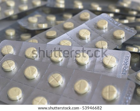 Yellow tablets in push-through strip - stock photo
