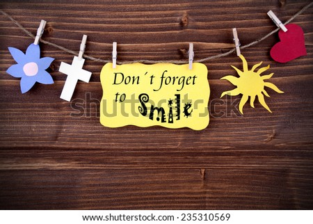 Yellow Tag Or Label With Heart And Flower And Cross And Sun On A Line With Life Quote Dont Forget To Smile On Wooden Background, Four Symbols, Vintage, Retro And Old Fashion Style With Frame - stock photo