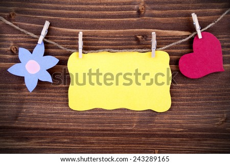 Yellow Tag Or Label With Heart And Flower On A Line With Copy Space Or Your Free Text Here On Wooden Background, Two Symbols, Vintage, Retro And Old Fashion Style With Frame - stock photo