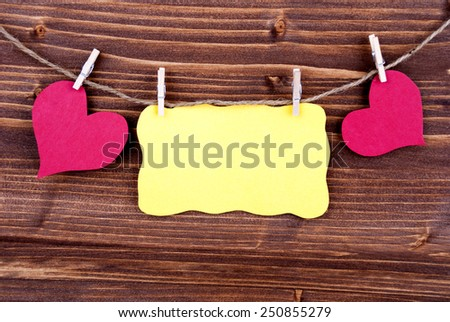 Yellow Tag Or Label With Two Hearts On A Line With Copy Space Or Your Free Text Here On Wooden Background, Two Symbols, Vintage, Retro And Old Fashion Style - stock photo