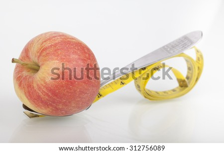 Yellow tape measure around spoon and red apple representing dieting - stock photo