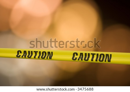 Yellow tape with the word caution on it across a warning light background - stock photo