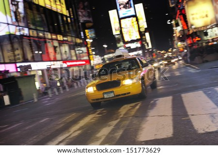 Yellow taxi on city street at night - stock photo
