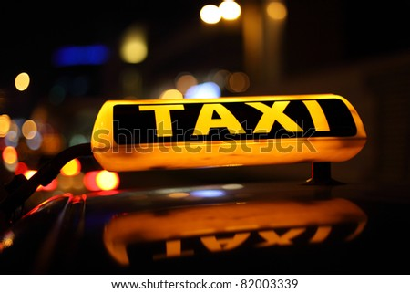 Yellow taxi sign at night - stock photo