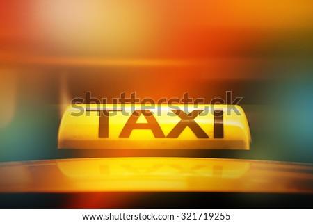 Yellow Taxi Sign on Car Rooftop, Street Light Bokeh, Selective Focus - stock photo