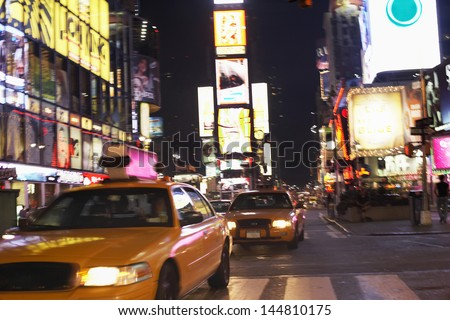 Yellow taxis on city street at night - stock photo