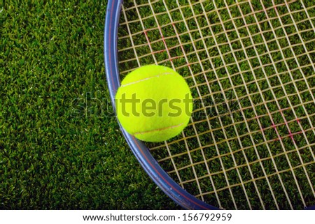 Yellow tennis ball and a racket over the grass - stock photo