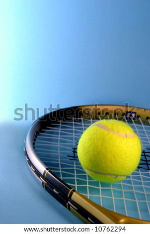 yellow tennis ball and racket over a blue background - stock photo