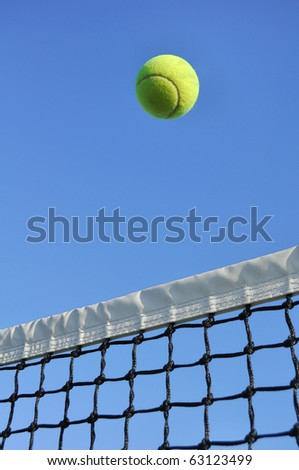 Yellow Tennis Ball Flying Over the Net Against a Clear Blue Sky