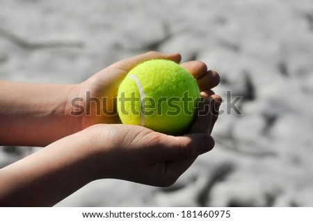 Yellow tennis ball, illuminated by the sun, lies in a child's hands.