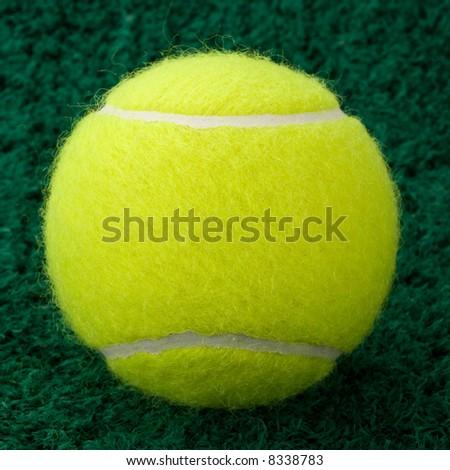 Yellow Tennis Ball Isolated On Astro Turf Background - stock photo