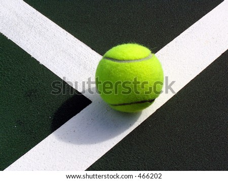 yellow tennis ball on the backcourt line - stock photo