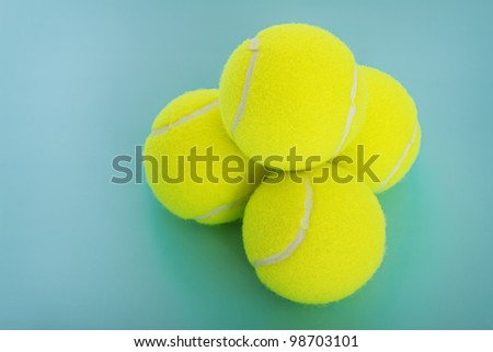 Yellow tennis balls on a blue background. - stock photo