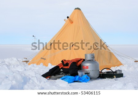 Yellow tent and camping equipment - stock photo