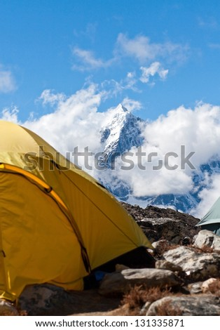 Yellow tent at mountain base camp - stock photo