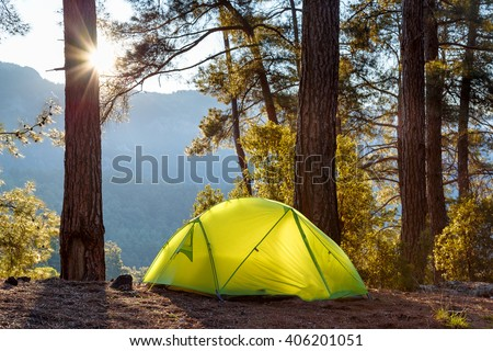 yellow tent in morning forest - stock photo
