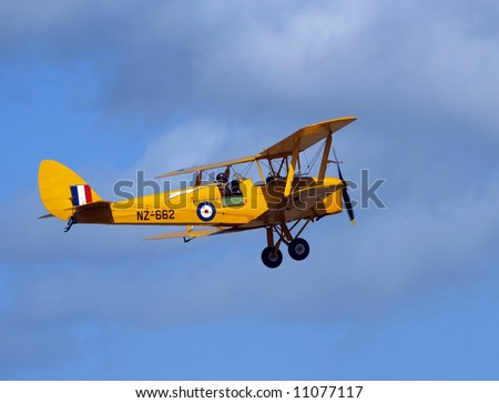 Yellow Tiger Moth showing pilot with long white scarf - stock photo
