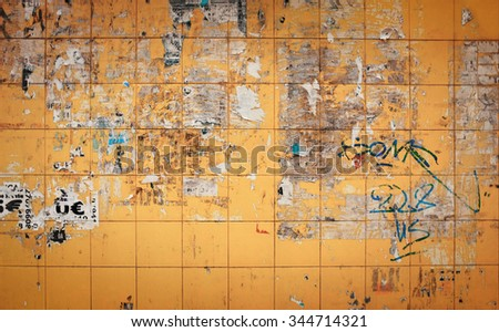 Yellow tiled wall with remains of ripped paper from advertising posters - stock photo