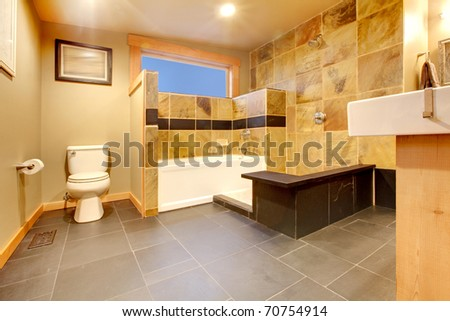 Yellow tiles, black floor and modern design of the large bathroom - stock photo