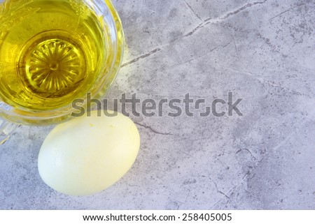 Yellow tinted liquid in a glass teacup with a freshly dyed yellow Easter egg laying next to it. Top down perspective with a marble surface for your text and images. - stock photo