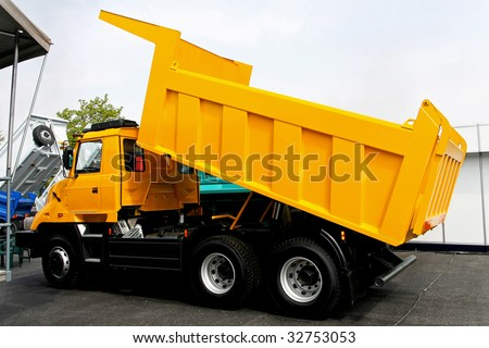 Yellow tipper dump truck for construction work - stock photo