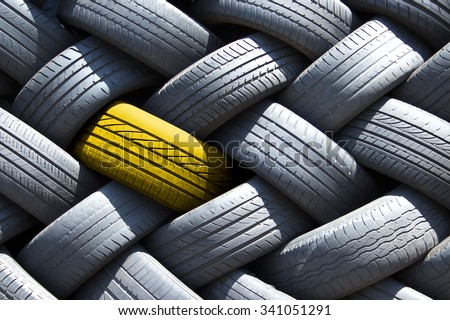 Yellow tire in a stack of tires - stock photo