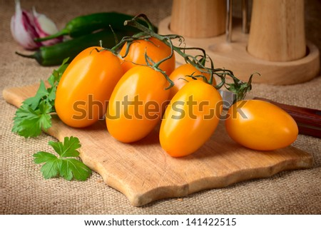yellow tomatoes and parsley on chopping board - stock photo