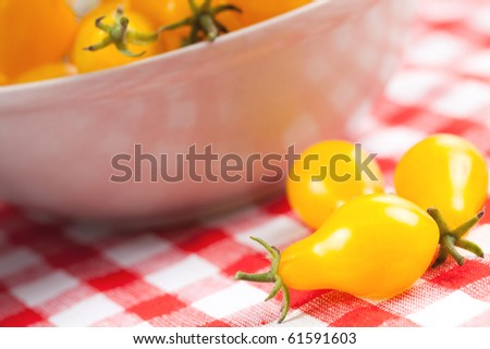 yellow tomatoes on picnic tablecloth - stock photo