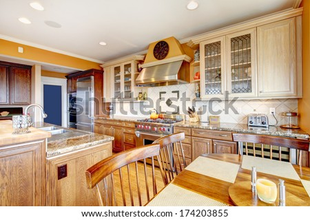 Yellow tones kitchen with tile decorated backsplash, kitchen appliances and dining table set - stock photo