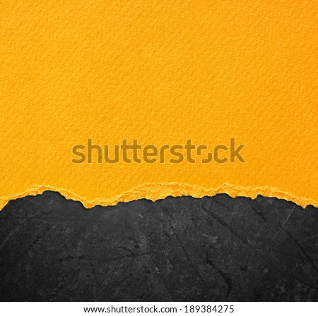 yellow torn paper over black background - stock photo