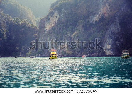 Yellow tourist ship in beautiful seascape of Phi-Phi islands, Krabi, Thailand. Image with selective focus and toning - stock photo
