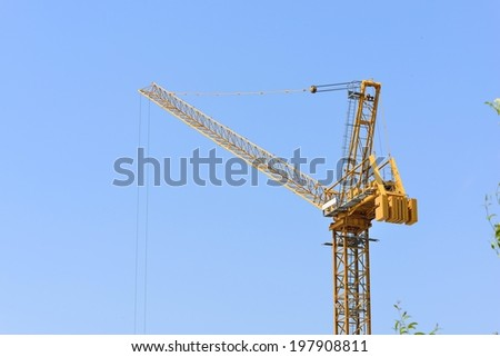 yellow tower crane at construction site in sunny day - stock photo