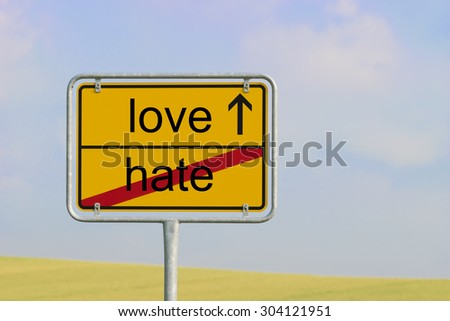 """Yellow town sign with text """"hate love"""" - stock photo"""