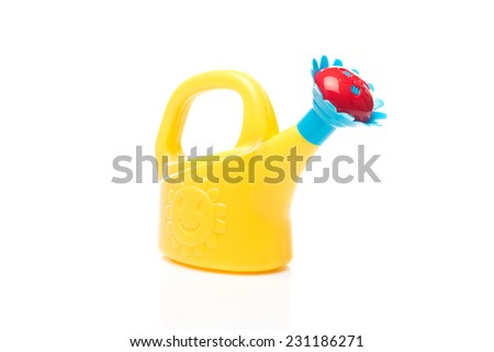 Yellow toy watering can against a white background - stock photo